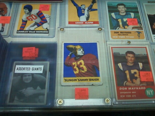Image description: trading cards featuring white football players in plastic holders fill a display case.