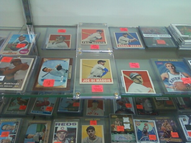 Image description: approximately 26 baseball and basketball cards featuring white and black baseball players in plastic holders fill a display case.