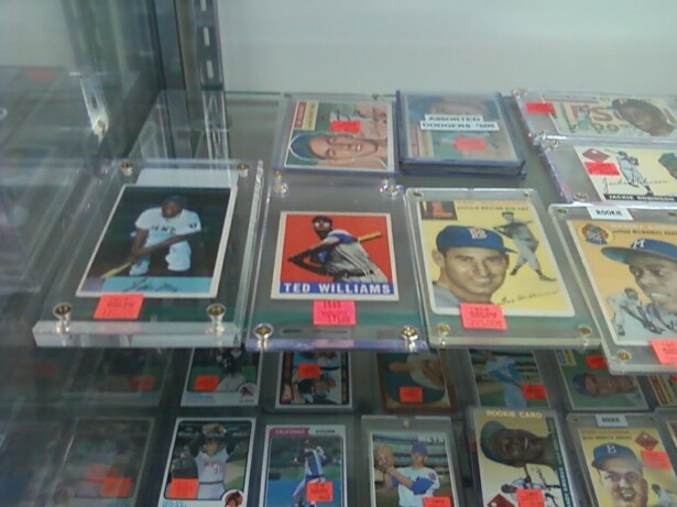 Image description: baseball cards featuring white and black baseball players in plastic holders fill a display case.