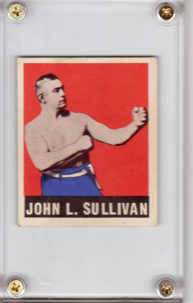 "Image description: a 1948 Leaf Boxing John L. Sullivan trading card, in a plastic holder with gold screws. Boxer John L. Sullivan, a shirtless white man wearing blue pants with a white belt, assumes a boxing stance against a red background with a white border. Below him, ""JOHN L. SULLIVAN"" is printed in white letters on a black background."