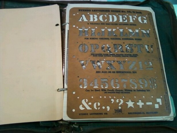 "Image description: interior of a scrapbook shows, at left, a blank beige page, and at right, a brown stencil, about standard 8 1/2"" by 11"" binder size. Stencil contains the alphabet, numbers 1 through 9, and a about a dozen symbols."