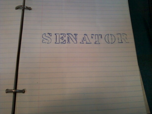 "Image description: a ruled piece of binder paper, in a scrapbook, with ""SENATOR"" stencilled across the center of the page in blue ink."