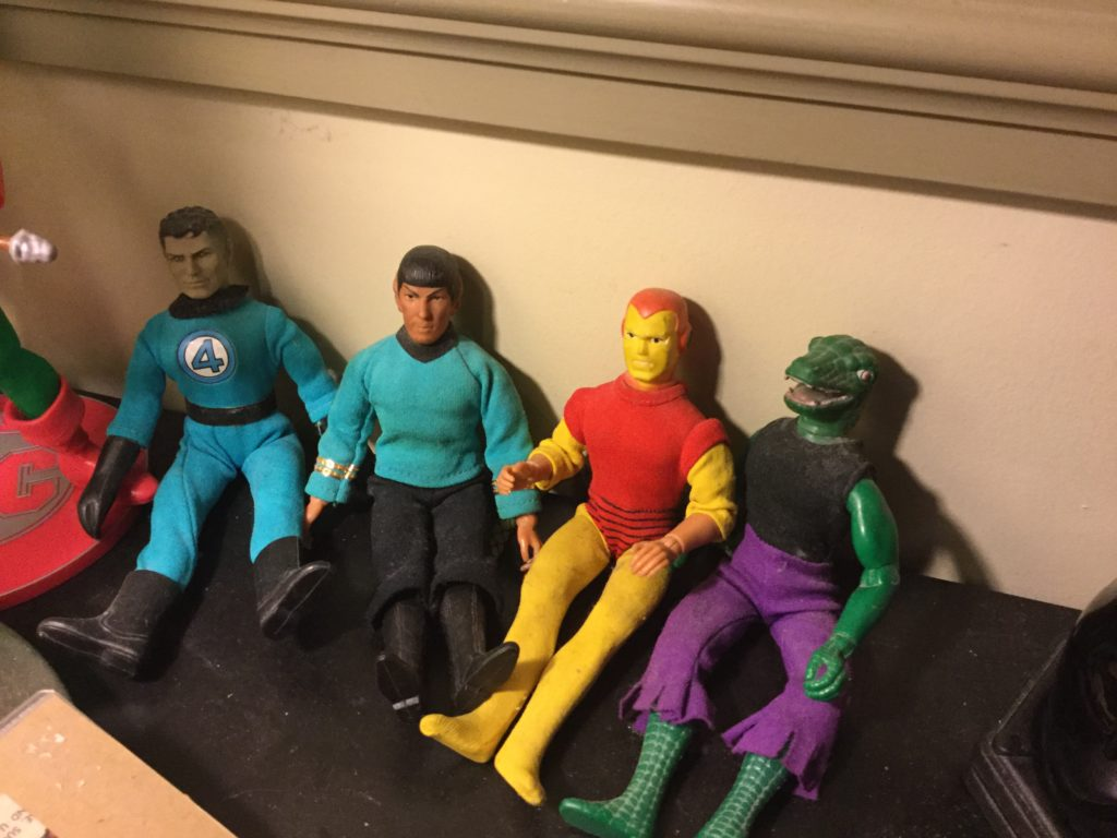 Mego's World's Greatest Super-Heroes and Star Trek figures sit on a desk. From left to right, Mr. Fantastic, Mr. Spock, Iron Man and The Lizard.