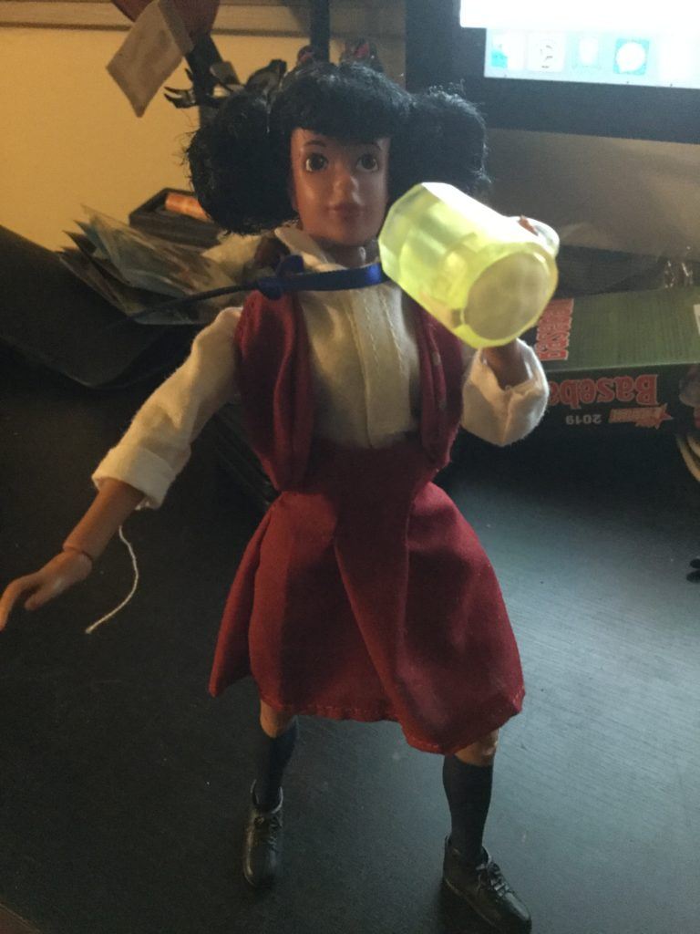 A Mego Tootie action figure from The Facts of Life series, a teenaged looking female doll with black hair and brown skin in a maroon and white private school uniform, drinking a mug of beer.