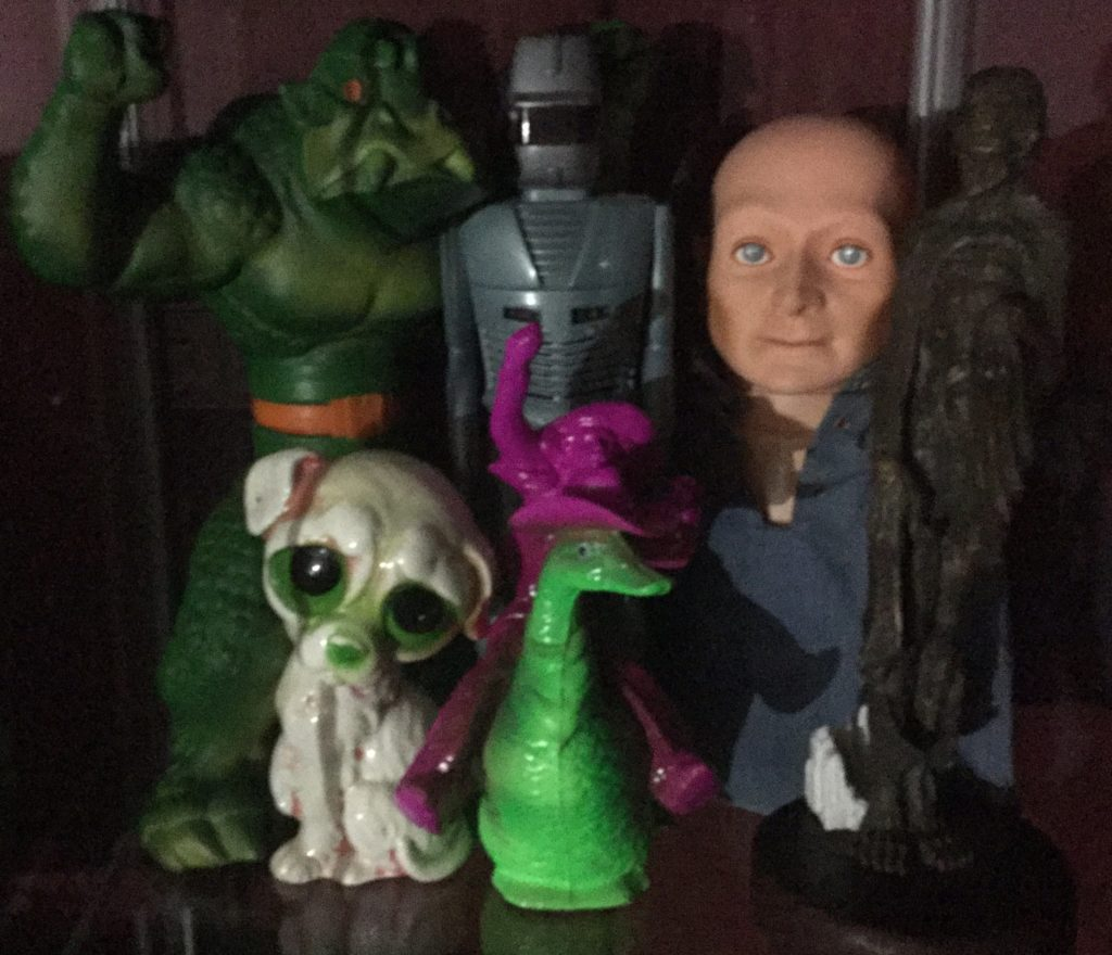 Various toys and sculptures sit on a shelf: Ideal's KRUSHER doll, a green monster with orange trim; ROM The Spaceknight, a grey robot with red trim; Hugo, the Man of a Thousand Faces, a bald puppet with white skin wearing a blue denim shirt; a statue of a vampire version of comic book character The Joker; a green, pink and white ceramic statue of a sad looking dog with large green and black eyes; A green duck wearing a pink cowboy hat, being ridden by a pink cowboy.