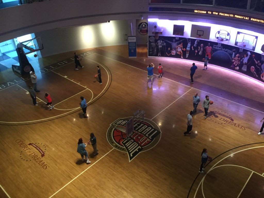 An overhead shot of the basketball courts of the Naismith Memorial Basketball Hall of Fame in Springfield, MA. approximately 15 people play basketball near a number of basketball hoops, in a circular basketball gym with pictures of famous basketball players off in the distance.