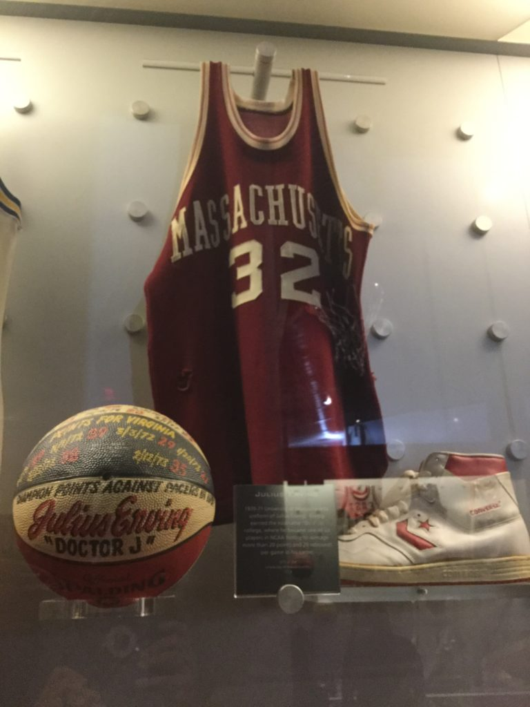 The Julius Erving display case at the Naismith Memorial Basketball Hall of Fame in Springfield, MA. A University of Massachusetts maroon and white basketball jersey, an inscribed red, white and blue basketball, and a white Converse basketball sneaker with red trim are visible in the case, along with a placard that is not legible.