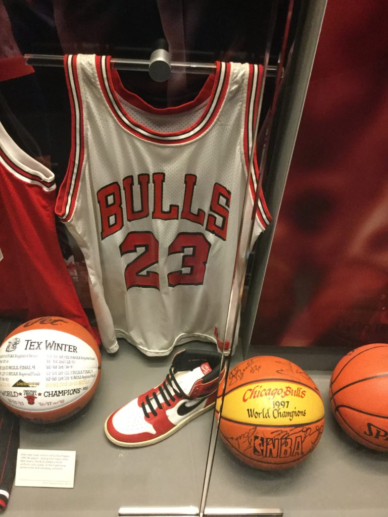 The Michael Jordan display case in the Naismith Memorial Basketball Hall of Fame in Springfield, MA. A Chicago Bulls #23 jersey, white with red trim, once worn by Michael Jordan, a red and white Nike Air Jordan sneaker, and several inscribed basketballs are visible in the case in this picture.
