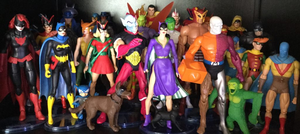 A picture of approximately 25-30 action figures of DC Comics super-hero characters.