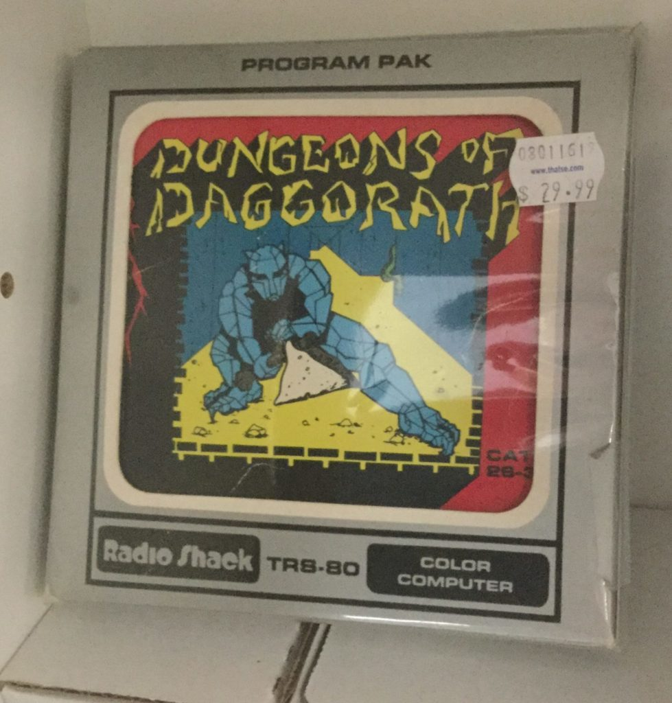 A picture of a boxed Dungeons of Daggorath cartridge for Radio Shack's TRS-80 Color Computer. a blue-gray gargoyle points a sword at the camera in a maze with a yellow floor and bluew walls, with yellow and black Dungeons of Daggorath logo floating above him. Picture is framed by red trim. Box of cartridge is grey, with black trim and lettering around the outside, and white inner window trim near the window the cartridge is displayed in.