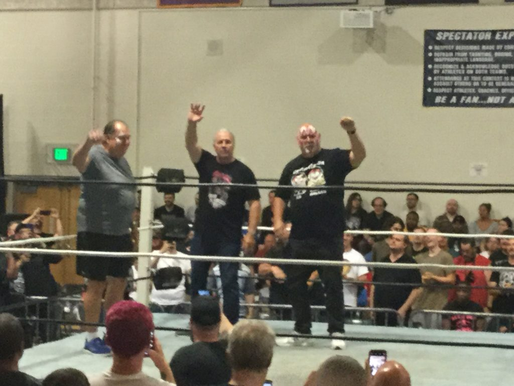 "Demolition Ax (Bill Eadie, left, a man with black hair and white skin wearing a grey t-shirt, shorts and blue sneakers), Bret ""The Hitman"" Hart (center, a man with grey hair and white skin, wearing a black t-shirt and black jeans) and and Demolition Smash (Barry Darsow, right, a bald man with white skin, wearing a black t-shirt, black jeans and white sneakers) stand in a wrestling ring and wave to the crowd at a Blitzkrieg Pro/Big Time Wrestling event at CREC Civic Leadership High School in Enfield, CT on August 24th, 2019."
