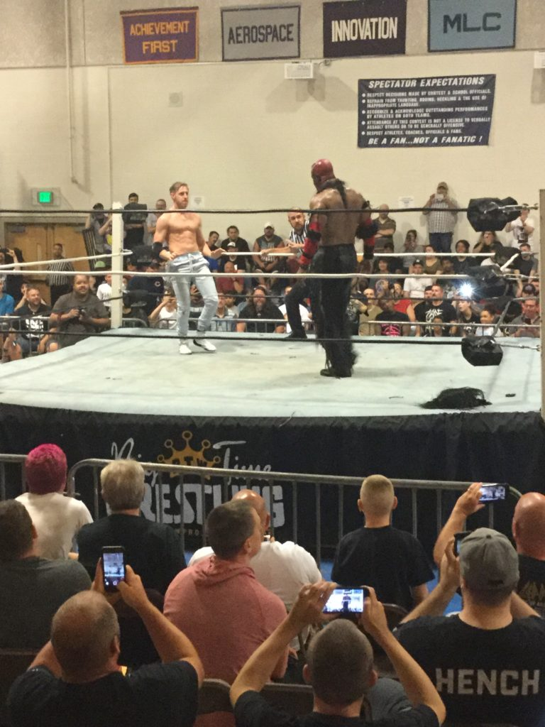 Orange Cassidy (left, a shirtless man in blue jeans with reddish blonde hair and white skin) faces The Boogeyman (right, a shirtless man with brown skin, head painted red, wearing black pants) as the crowd looks on at a Blitzkrieg Pro/Big Time Wrestling event, August 24th, 2019.