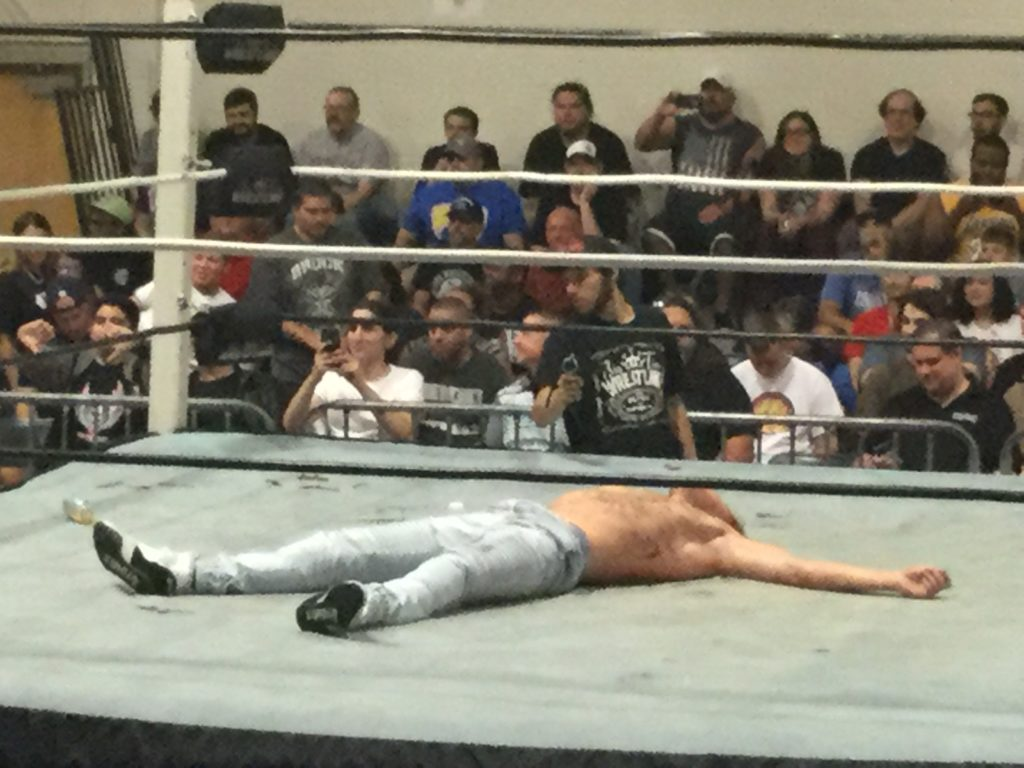 Professional wrestler Orange Cassidy (center, a shirtless man with white skin, wearing blue jeans and white sneakers with black soles) lies motionless in a wrestling ring as a crowd looks on at a Blitzkrieg Pro/Big Time Wrestling event, August 24th, 2019.