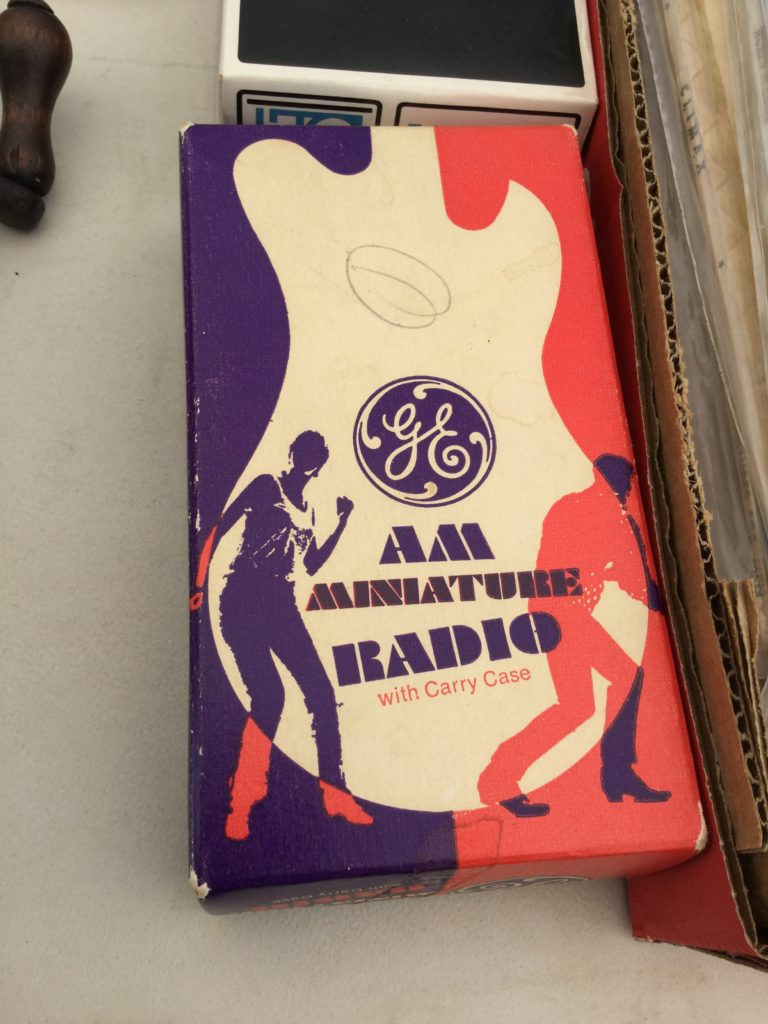 A box for a GE AM Miniature Radio with Carry Case from the late 1960s. On it, there are silhouettes of a man and woman dancing, and the body of an electric guitar, both inset on a background that's purple on the left side and orange on the right. The parts of the man and woman that show up against the backgrounds instead of the guitar are the opposite color of the main background (orange for left, purple for right).