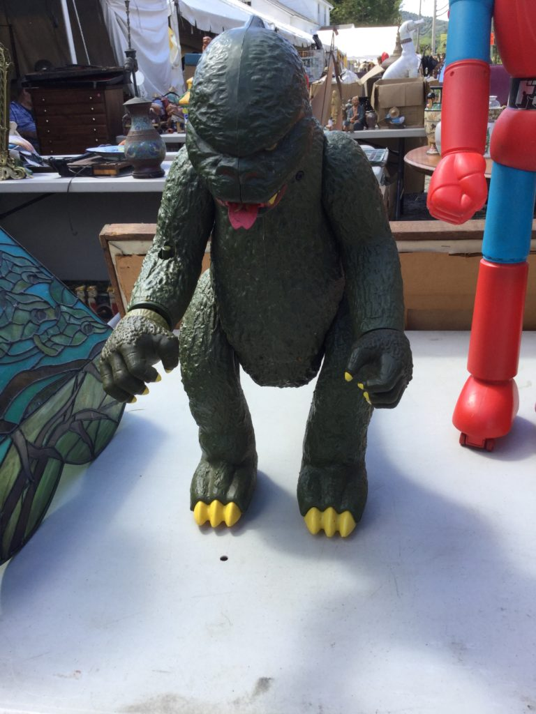 "A 1970s Mattel Godzilla toy (a green action figure-type toy standing about 18"" high with yellow claws, teeth and eyes, and a red strip of fire in its mouth that resembles a tongue) stands on a table, with a blue and green glass Tiffany lamp to its left, and a Mattel Shogun Warriors Dragun toy (also a large action figure, but a blue, red and black robot) to its right. More tables of antiques are visible in the background."