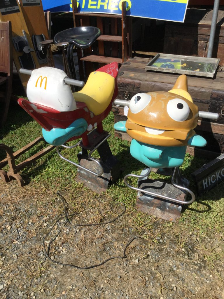 Two small, older McDonald's playground rocking horse-ish rides sit on green grass, with a patch of brown dirt and gravel in front of it at Brimfield Antiques Market, with other antiques in the background. At left, a red white and yellow boat with a McDonald's logo on the mast, silver handles, and a teal simulated sliver of ocean water at the bottom. At right, a similar ride, but the ride is an anthropomorphic Filet-O-Fish sandwich (a brown roll, brown fish filet, white tartar sauce to simulate the appearance of a tongue, wide white eyes with black pupils, and teal fins) instead of a boat.