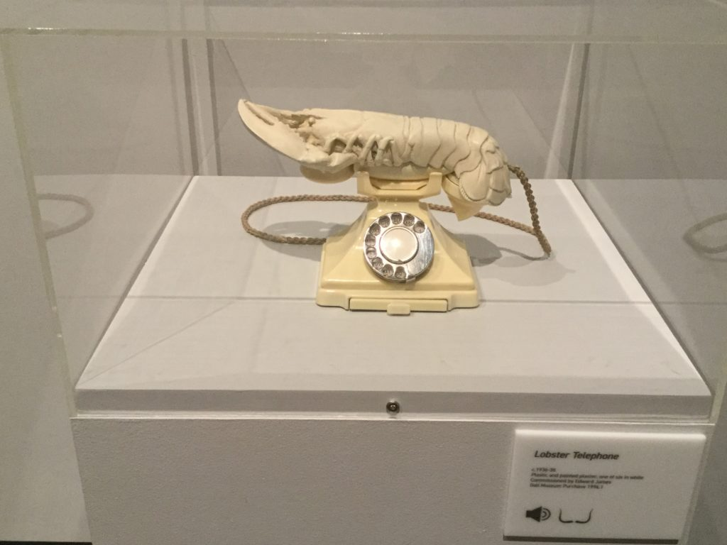 "Salvador Dali's ""Aphrodesiac Telephone"" sculpture, which is a sculpture of an ivory-colored rotary telephone with an ivory-colored lobster replacing the phone receiver. The link directly below this image and its caption goes to the Dali Museum's page on the sculpture, and gives a detailed description of the sculpture and its history."
