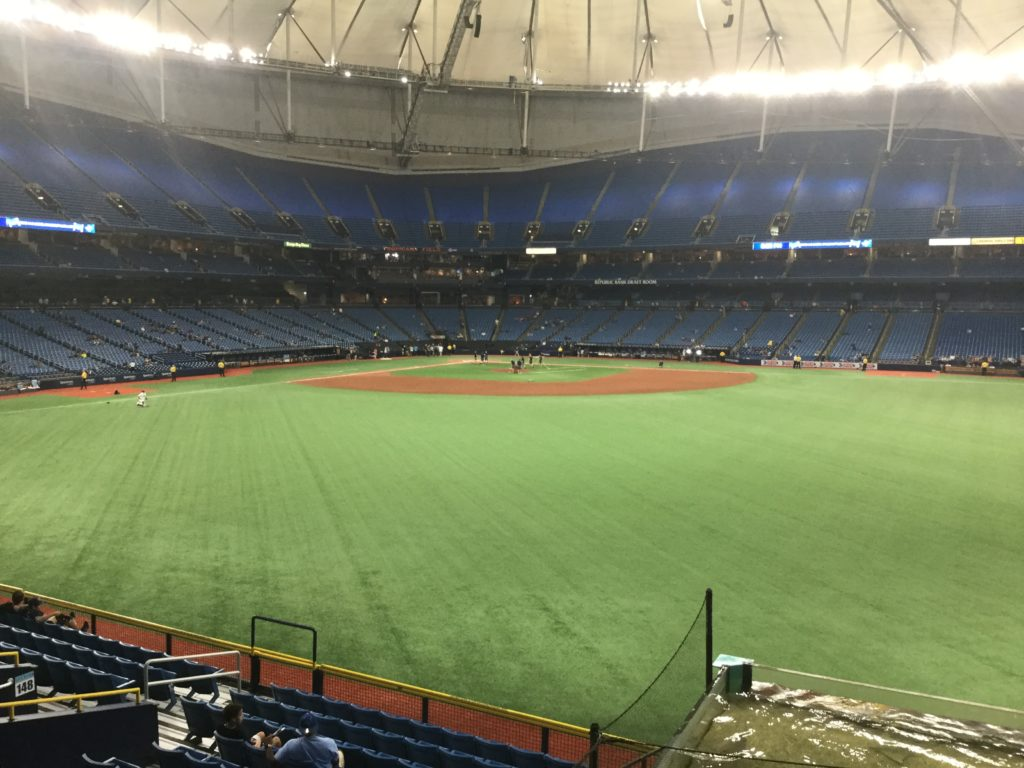 Interior shot of Tropicana Field, taken from right-center field. Green artificial turf and brown infield dirt can be seen, and blue seating is visible on the other side of the field, as well as an off-white roof.