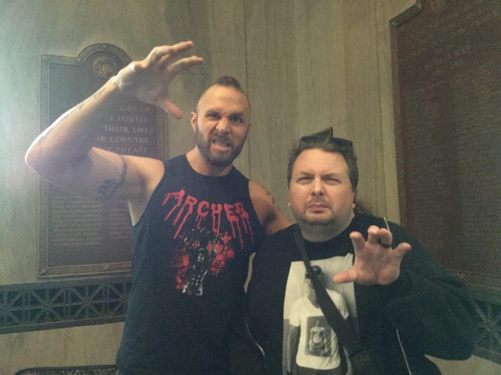 """Professional wrestler Lance Archer (left), a tall man with white skin, several arm tattoos, a dark brown beard, a hint of dark brown hair with a red braid weaved into it, and a black t-shirt that says """"ARCHER"""" across the top of it in bloody looking red letters, raises his right hand above his head in a claw position and makes a mean looking face, next to the author of this piece (right), a man with white skin, brown hair with black sunglasses on top of it, a brown goatee, wearing a black hooded sweatshirt and a black t-shirt with a black and white picture of a man on it that's obscured by a black bag strap. The man is also making a mean face, and is making a claw gesture with his left hand. Bronze laques are visible on the marble walls behind the two men."""
