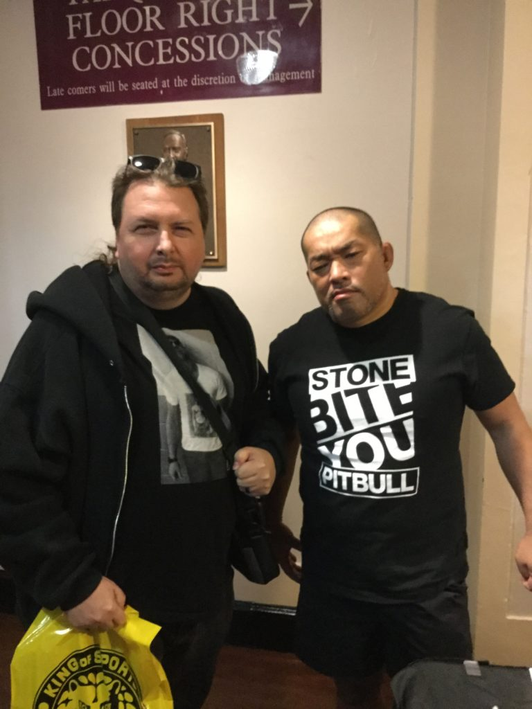 "At left, the author, a man with white skin and brown hair (with sunglasses in it), wearing black clothing, holding a yellow New Japan Pro-Wrestling shopping bag. At right, New Japan Pro-Wrestling's Tomohiro Ishii, a stern-looking Japanese man with a bald head, wearing black shorts and a black t-shirt that says ""STONE PITBULL BITE YOU"" on it."