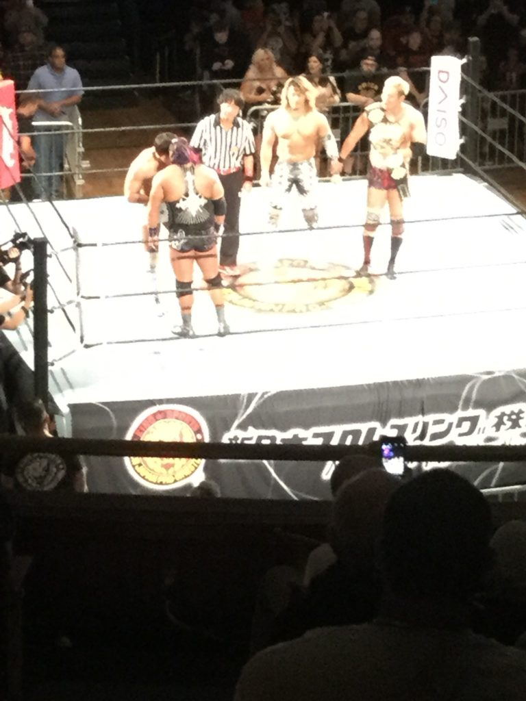 "In a wrestling ring, New Japan Pro-Wrestling wrestlers Kota Ibushi (far left, a shirtless Japanese man with short, dark brown hair) and EVIL (just below Kota Ibushi, a Japanese man in black and white singlet with purple ponytail) stand head to head at left, with referee ""Red Shoes"" Unno (a Japanese man with black hair in black and white referee uniform, black pants, and red shoes) and wrestlers Hiroshi Tanahashi (a Japanese man with long bleached blonde to brown hair, in black and white spandex pants) and Kazuchika Okada to their right (a Japanese man with short bleached blonde hair, in red tights and boots, holding the IWGP Heavyweight Championship belt over his right shoulder)."