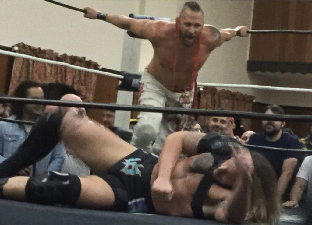 "Professional wrestler Lance Archer, a shirtless man with white skin and a red ""murderhawk"" hairstyle, stands at the back end of a wrestling ring and prepares to attack fellow pro wrestler Josh Briggs, a man with white skin and brown hair in black wrestling trunks and various knee and shoulder braces, laying prone at the front of the wrestling ring, at a Beyond Wrestling show in Worcester, MA."