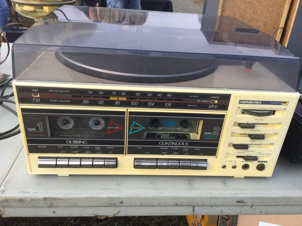 A beige 1980s-era Soundesign stereo system sits on a flea market table.