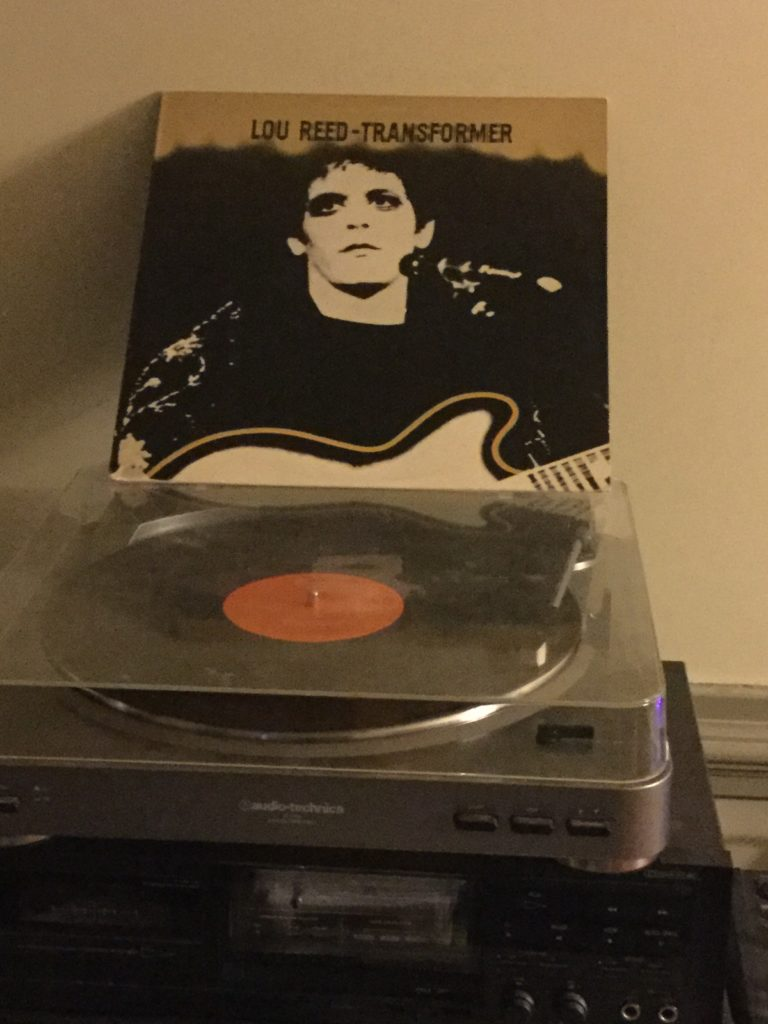"A copy of Lou Reed's ""Transformer"" album plays on a turntable, with the album cover (featuring a black and white picture of Lou Reed, wearing makeup, and holding a guitar while standing at a microphone) standing on top of the turntable cover."