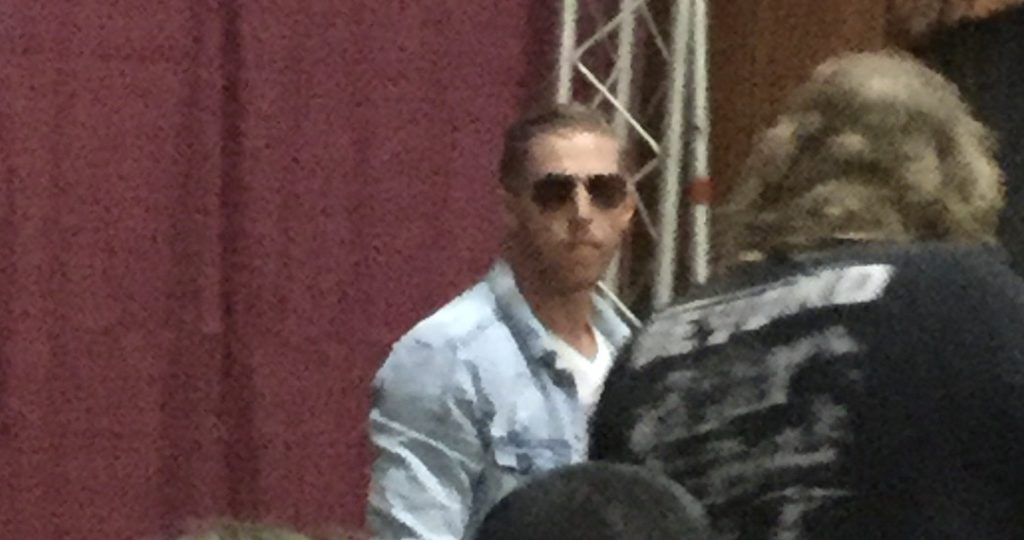 Professional wrestler Orange Cassidy, a man with white skin, red hair, and brown aviator sunglasses, wearing a light blue jean jacket and a white t-shirt, looks directly at the camera from a distance in front of a maroon curtain at a Beyond Wrestling show in Worcester, MA, as a photographer to his right tries to get a picture of him.
