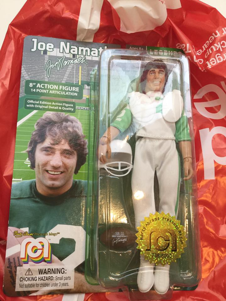 "A Mego Joe Namath 8"" action figure in its original package rests on top of a red and white bag. Football player Joe Namath, a smiling white man with brown hair, in a white uniform with green trim, with helmet and football. On the package's card, to the left of the figure, there is a picture of Joe Namath in a green uniform with white trim, holding a football."