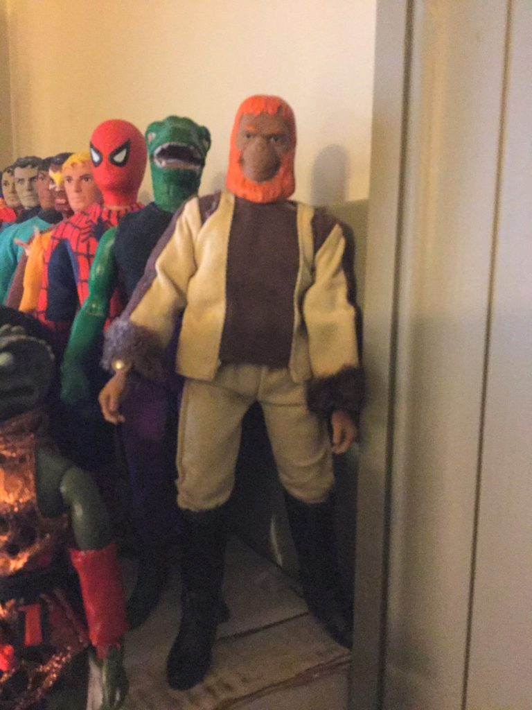 "Mego 8"" action figures. Top row: Planet of the Apes character Dr. Zaius, humanoid orangutan with orange hair in beige and brown outfit in front, with a number of other figures behind and next to him."