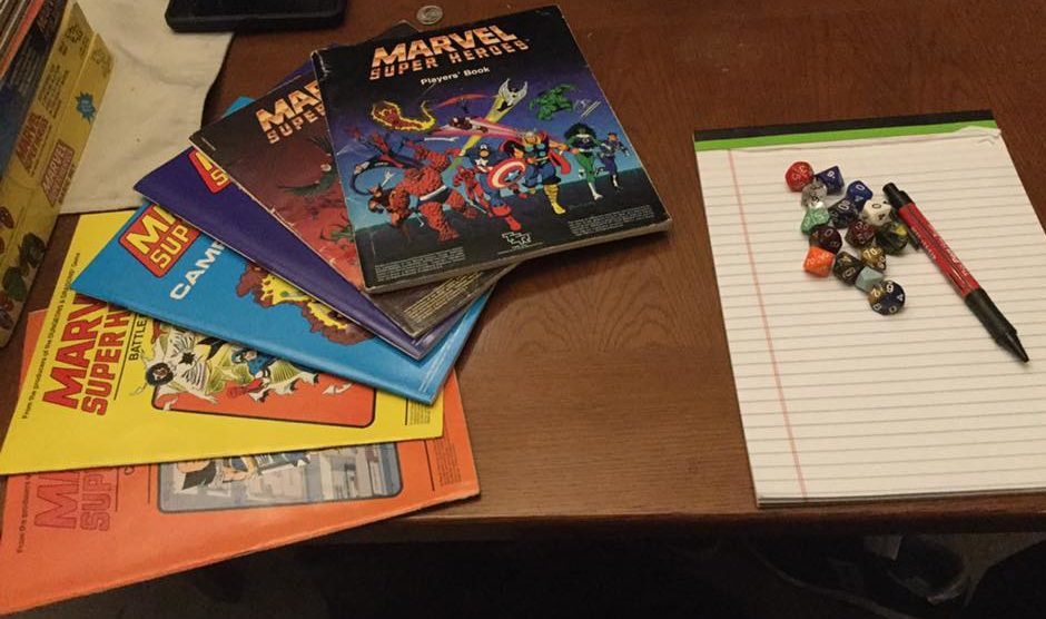 A selection of TSR Marvel Super-Heroes role-playing game handbooks, fanned out to the left, and a white legal pad with a pen and a large array of 10-sided dice to the right, on a brown table.