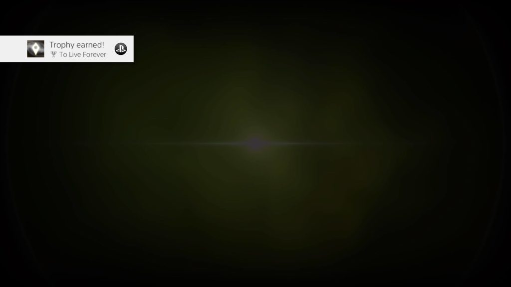 "Screenshot of someone getting the ""To Live Forever"" Trophy in the video game No Man's Sky. A faint, greyish-green sunburst in the center of a black screen, with the ""Trophy earned!"" Playstation Network icon at top left."