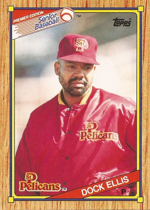 1989-1990 Topps Senior League baseball card of Dock Ellis, pictured in the center of the card, a man with brown skin and a black beard, wearing a red St. Petersburg Pelicans hat and warm-up jacket. Card has a woodgrain border, and logos from Senior League Baseball at top left, Topps at top right, and the St. Petersburg Pelicans at bottom left, with Docks name and abbreviation for his position, P for pitcher, at bottom right.