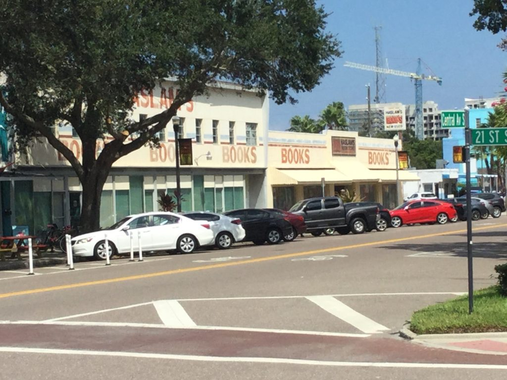 "Photo of Haslam's Book Store, St. Petersburg, Florida, taken from across Central Avenue South at 21st Street. A beige building with brick red painted letters that say ""HASLAM'S"" at the top level (obscured by a tree), and ""BOOKS"" near the top of the ground level in five different spots. Green curtains cover the windows of the building. A number of cars are parked in front of Haslam's, and the Central Av. S. and 21 St. S. signs are visible across the street."