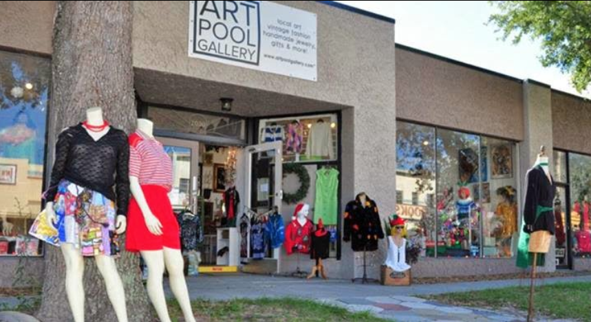 Mannequins stand outside ARTpool Gallery, St. Petersburg, Florida, in various poses. At front left, two mannequins in brightly colored clothing stand up against a tree.