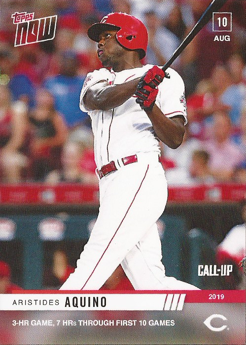 "A Topps Now card of Cincinnati Reds outfield Aristides Aquino (pictured; a man with brown skin in a white uniform with red trim, wearing a red batting helmet, and swinging a black baseball bat in front of a crowd at a stadium). The card reads ""Topps Now"" in the top left corner, ""10 Aug"" in the top right corner, ""Call-Up 2019"" with the Cincinnati Reds ""C"" logo in the bottom right corner, and across the bottom, in 2 lines, it reads ""Aristides Aquino"" and ""3-HR GAME, 7 HRs THROUGH FIRST 10 GAMES""."