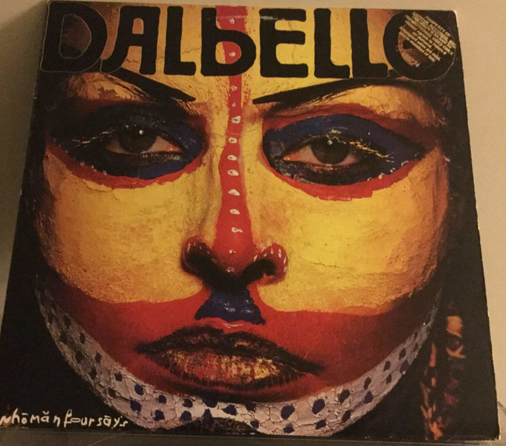 "The cover to Dalbello's ""whomanfoursays"" album. On the cover is a close-up of Lisa Dalbello's face, in yellow, red, blue, black and white tribal warpaint. the name ""Dalbello"" appears in black faux Cyrillic lettering at the top of the cover, and ""whomanfoursays"" appears in the bottom left in white scrawled lettering."