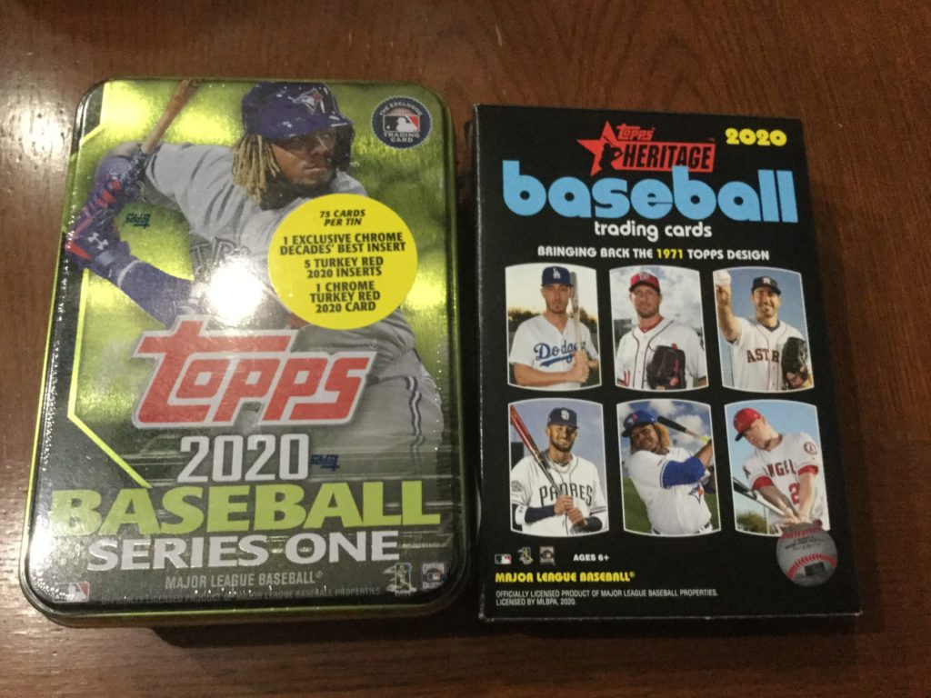 tin of 2020 Topps Series One baseball cards, and hanger box of 2020 Topps Heritage baseball cards on a brown table
