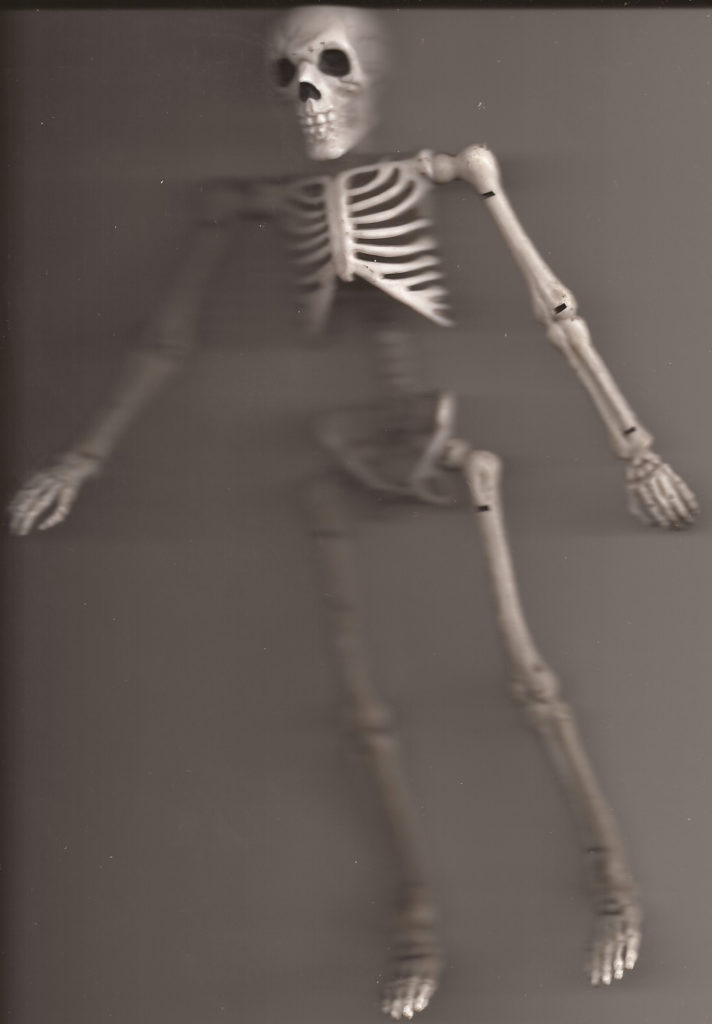 a plastic and rubber bendable action figure of a white skeleton lays on a scanner bed.