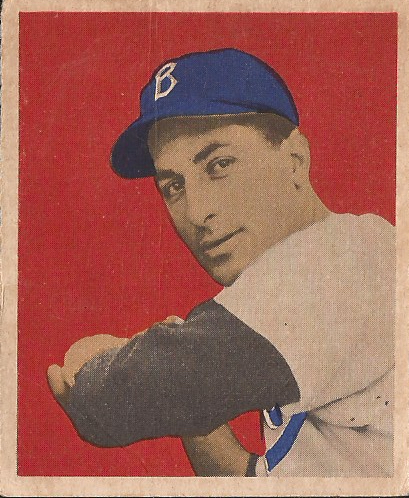 A 1949 Bowman Carl Furillo baseball card. Carl Furillo, a man with white skin and dark hair, wears a white Brooklyn Dodgers uniform with blue trim and a blue baseball cap with the letter B on the front of it, as well as a dark-colored undershirt. Carl's swinging a baseball bat, though only the hilt of the bat is visible. The card is only in partial color, as it was printed in greyscale with the blue highlights on the uniform, against a red background with beige trim.